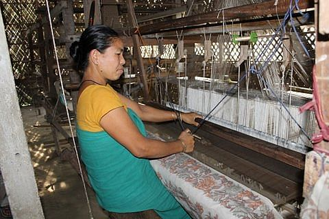 Miri, an Assamese woman from the nearby hills, weaving magical patterns into the silk saree at Sualkuchi