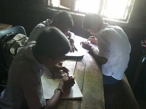 Children at the school stop to think for a minute, and then pick up their pencils and start drawing their vision of an ideal school.