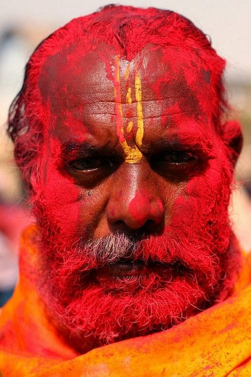 A temple priest bathed in red gulaal takes time out to pose for the camera.