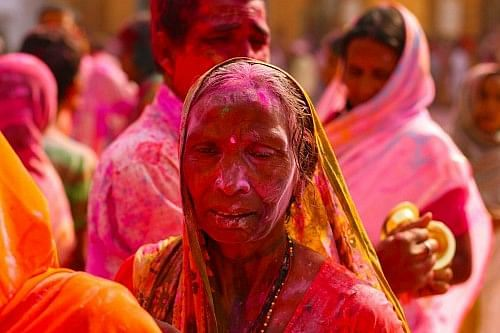 An elderly Indian lady playing Holi in the Sri Sri Radha Govinda temple.