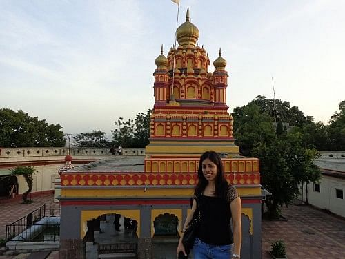 The writer standing against the façade of the Parvati temple