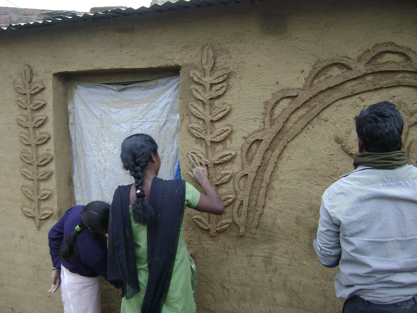 Display of art work on the walls of the community hall by the Santhals