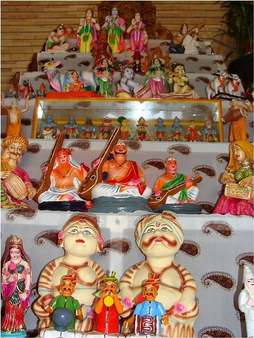 Dolls are set up on stairs with a kalash on top.