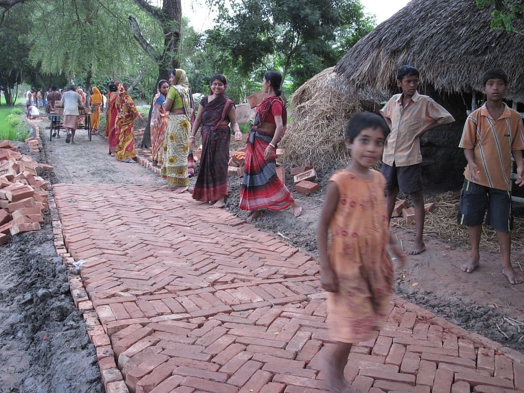 Lotika Sarkar, 23, who could not reach a health centre for an institutional delivery due to lack of connectivity, now energetically guides her friends in laying bricks for the road. (Credit: Saadia Azim\WFS)