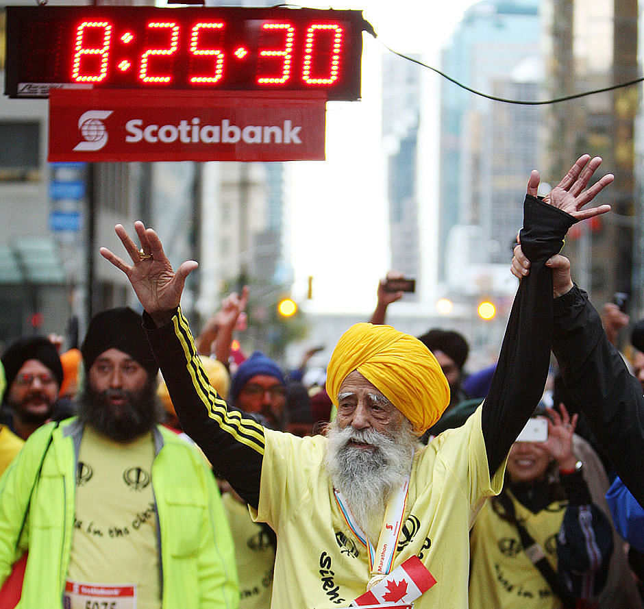 Fauja Singh waves to supporters minutes after finishing the 2011 Toronto Scotiabank Marathon