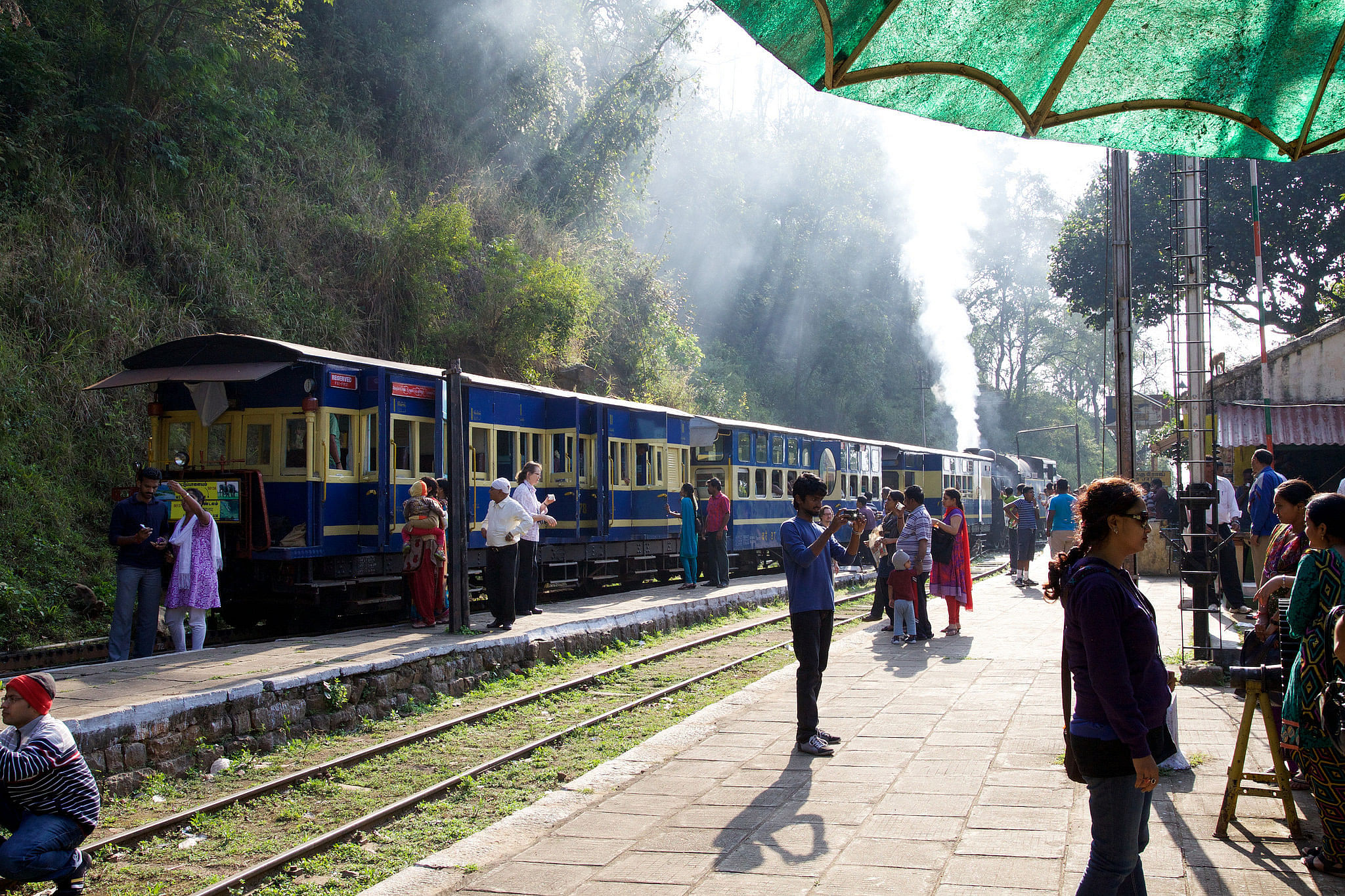 The Nilgiri Mountain Railway, cutting across the lush green hill side, with the engine at the back, pushing the train up the hills