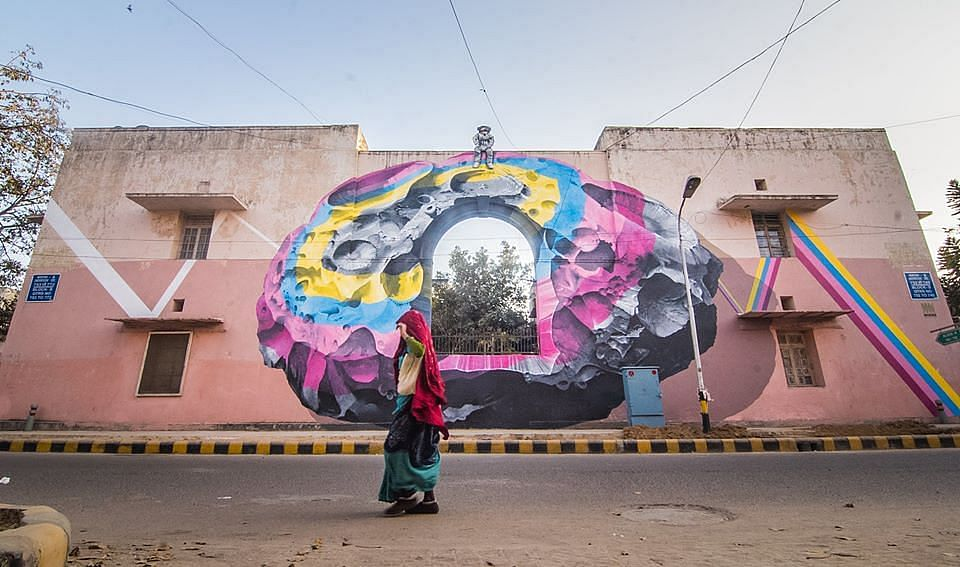 """""""The astronaut atop the wall is a metaphor for someone who can see things from a different perspective, as a silent viewer of a larger picture. In this case, he is a witness to all the daily activities of Lodhi colony."""""""