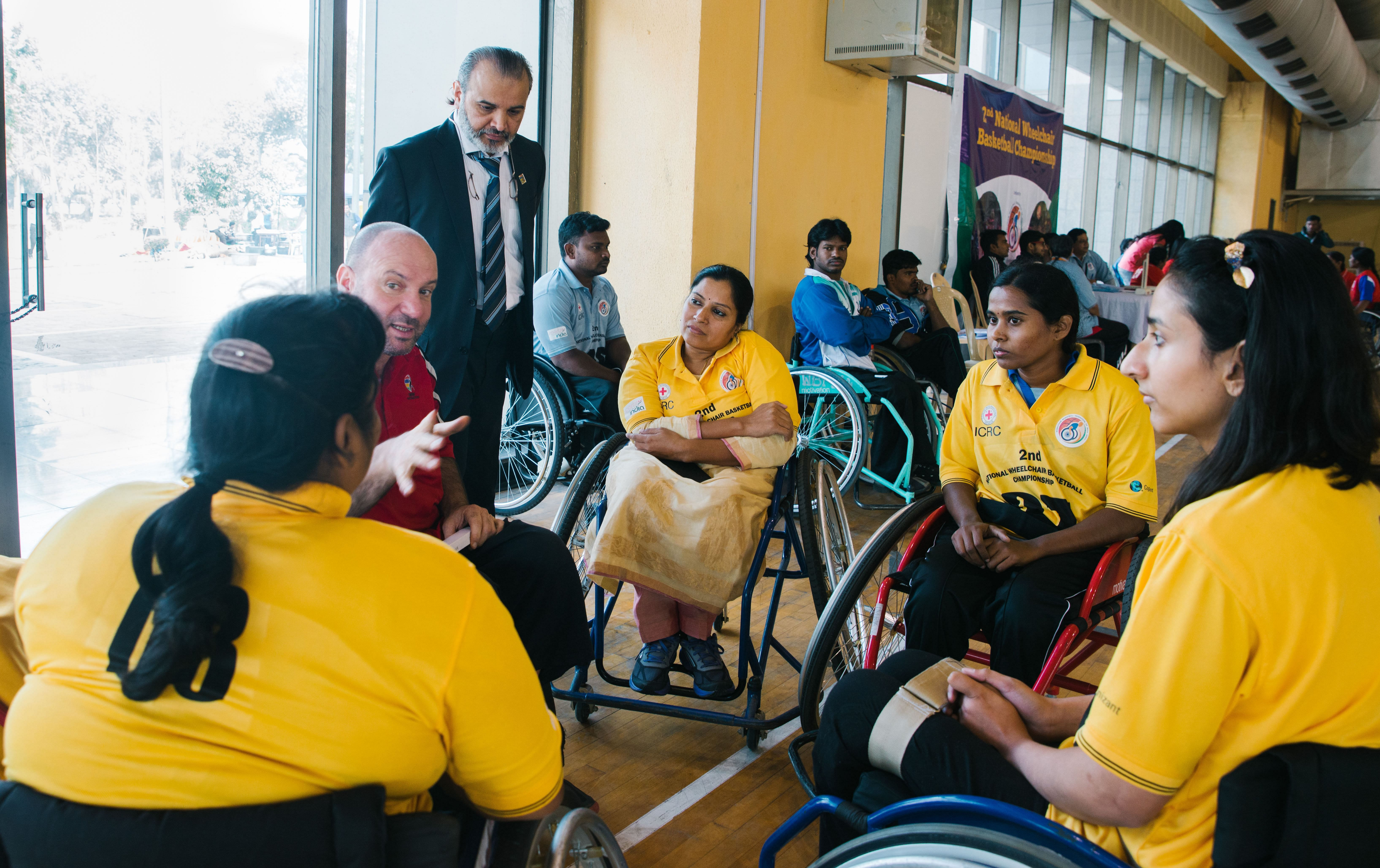 Madhavi with the first women's team at the National Wheelchair Basketball Tournament, pay attention to their coach during a timeout amidst the match.