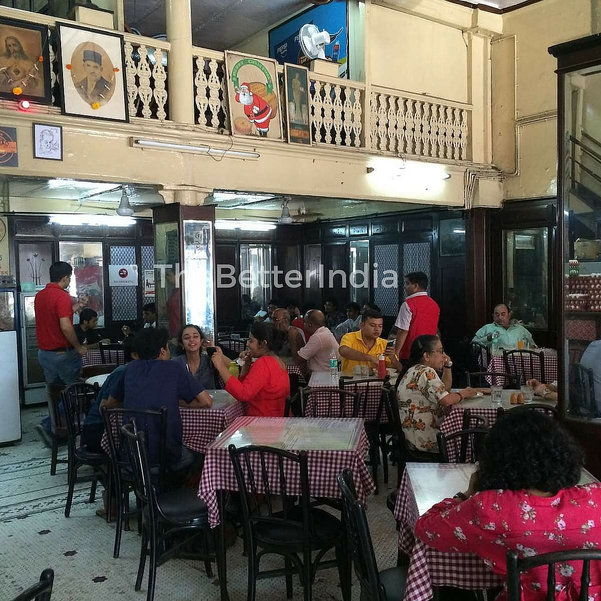A bustling Kyani Bakery with its dark, aged wooden tables, covered with the quintessential red-and-white checked tablecloth.