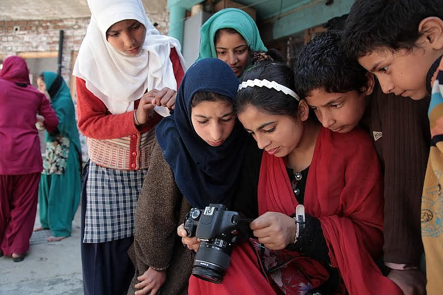 Girls learning to operate the camera at the Kupwara home.